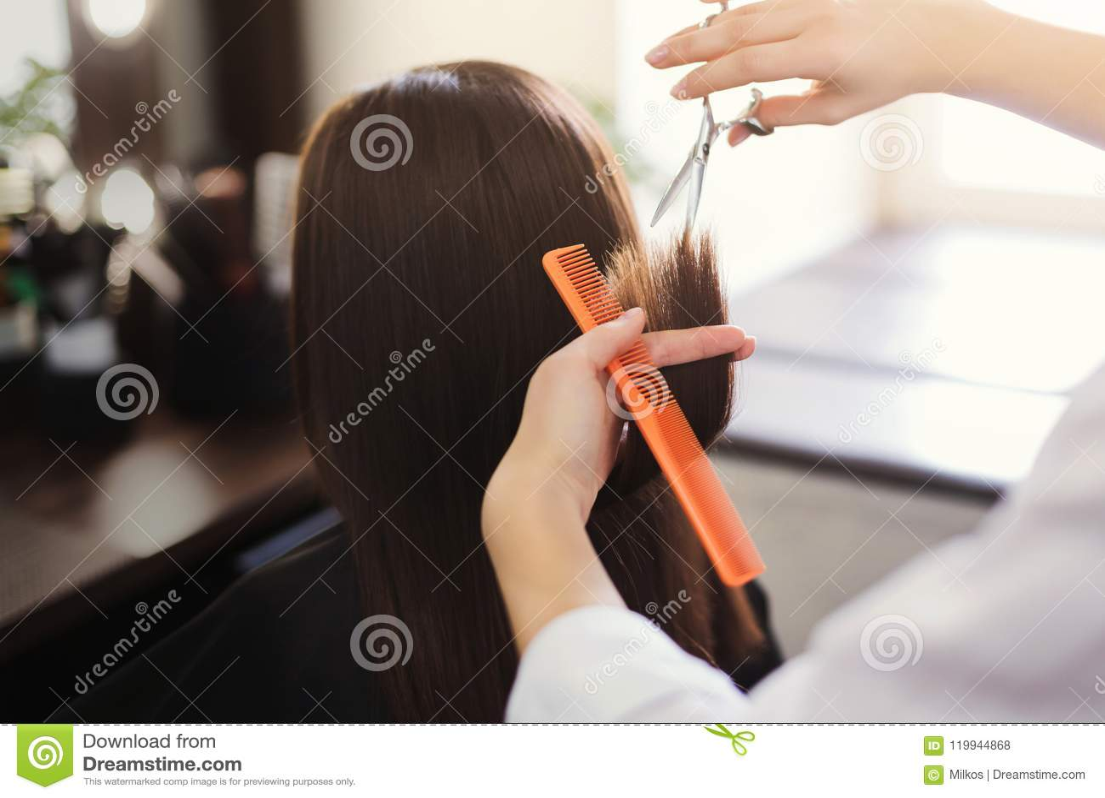 Parrucchiere che sistema capelli marroni lunghi con le forbici