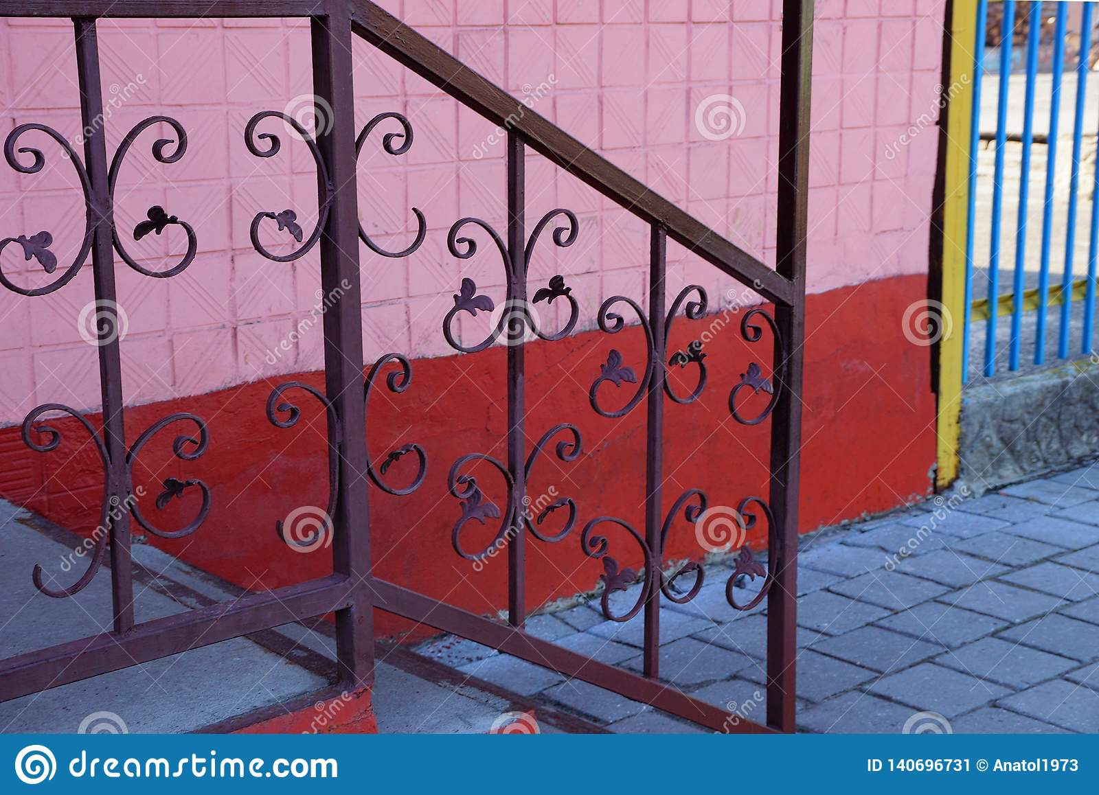 Part of the brown handrails with a forged pattern on the steps on the street near the wall
