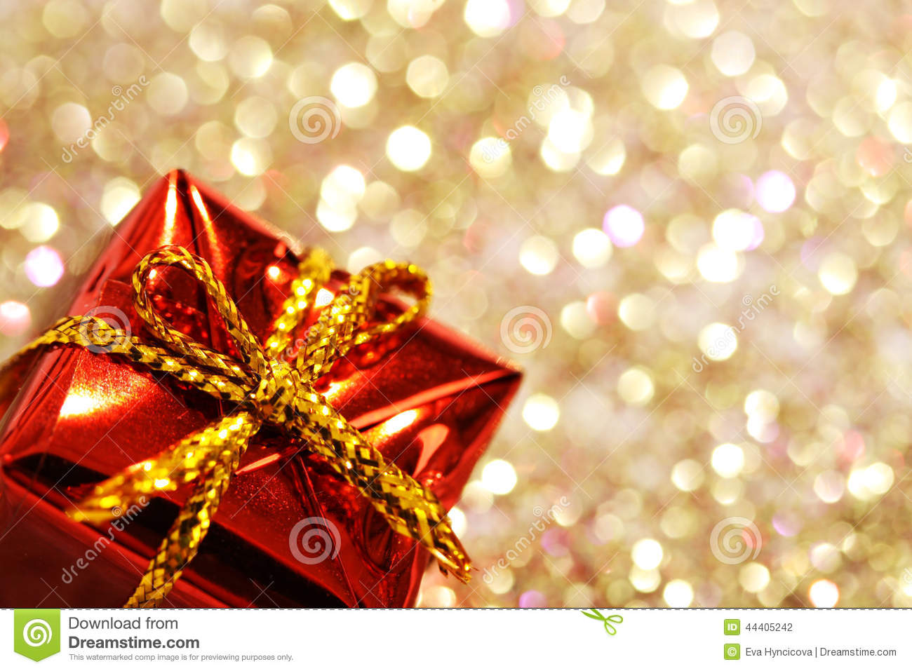 Part of christmas red gift box with yellow bow on glitter silver and gold background