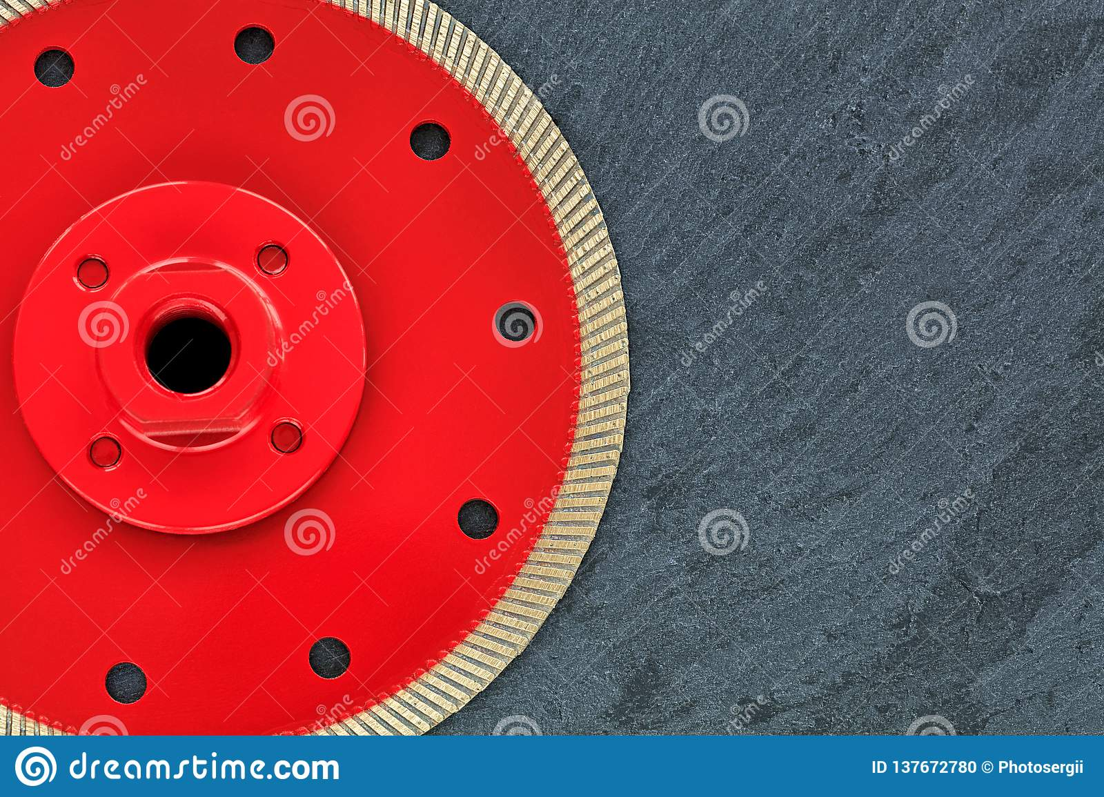 A part of a diamond cutting wheel is red with a threaded nut on a background of gray granite