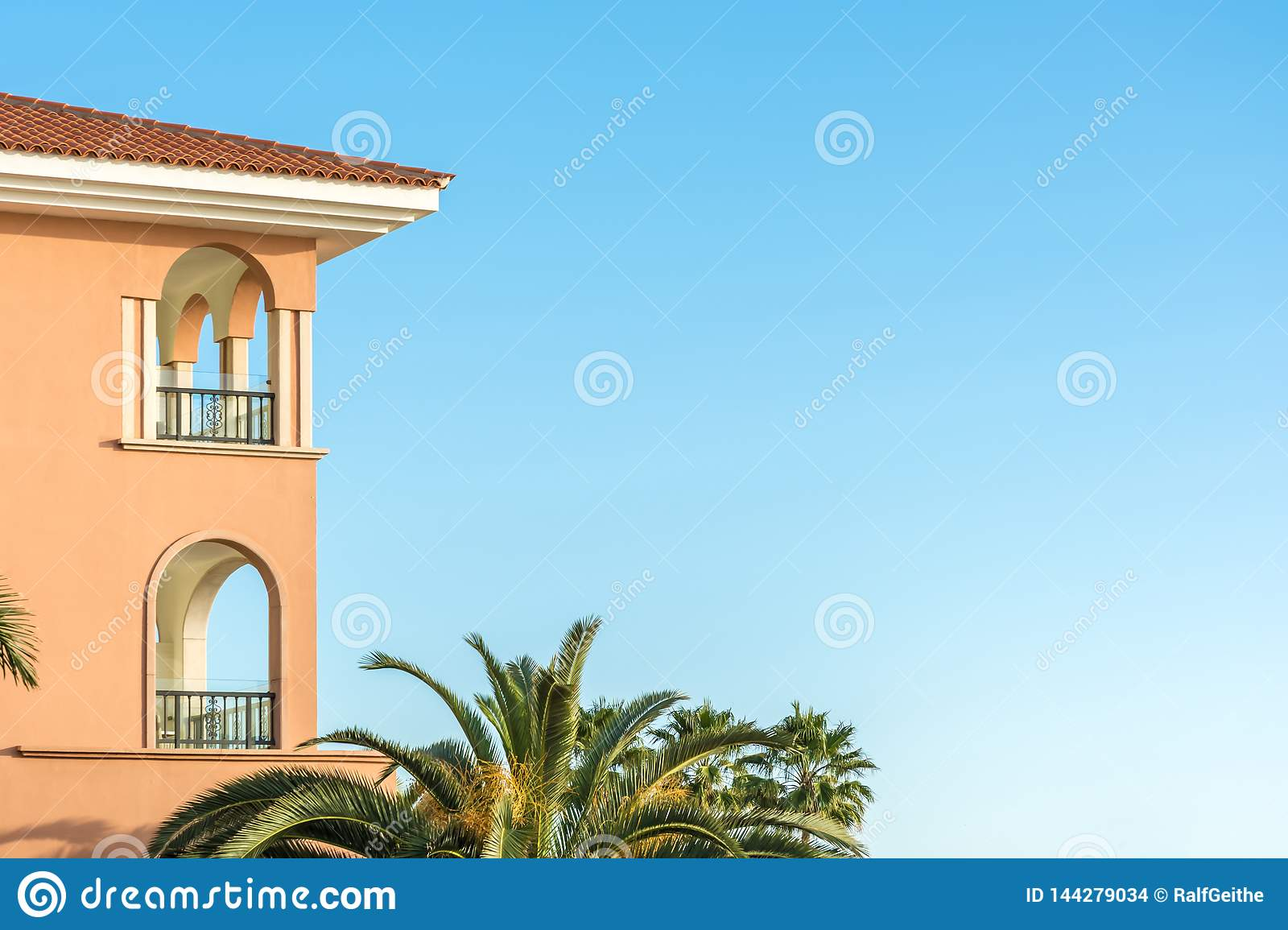 Part of a luxurious house in mediterranean style with palm trees and copy space in the blue sky