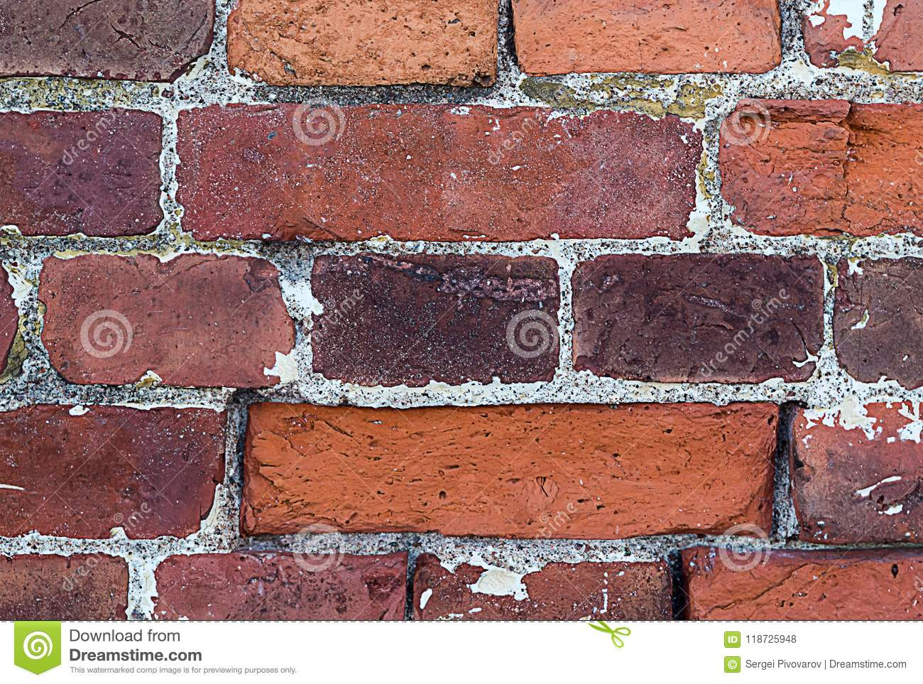 Part of an old weathered brick wall with cement lines seams rectangular blocks