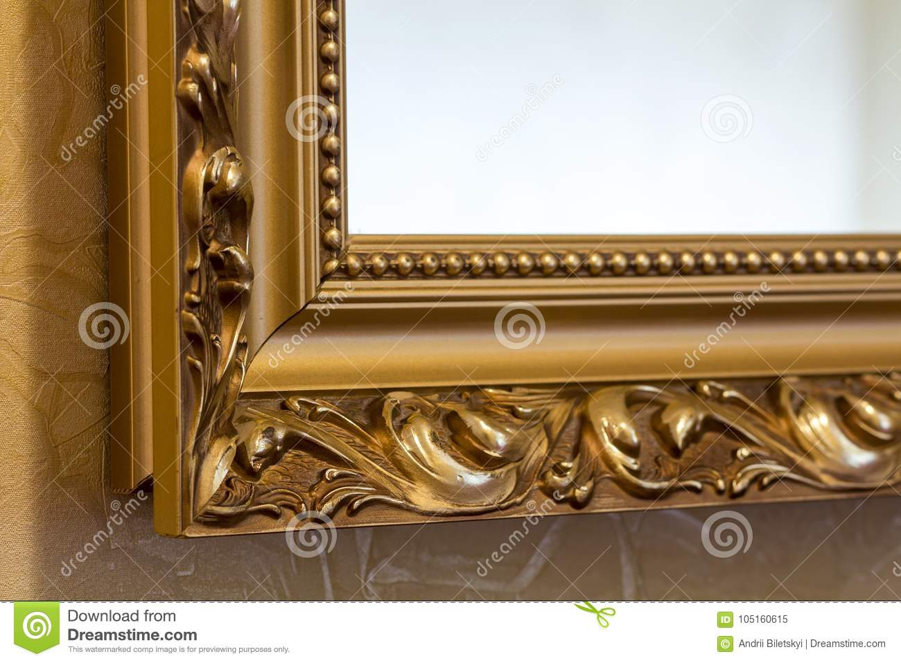 Part of the ornate, golden color carved mirror frame in ancient
