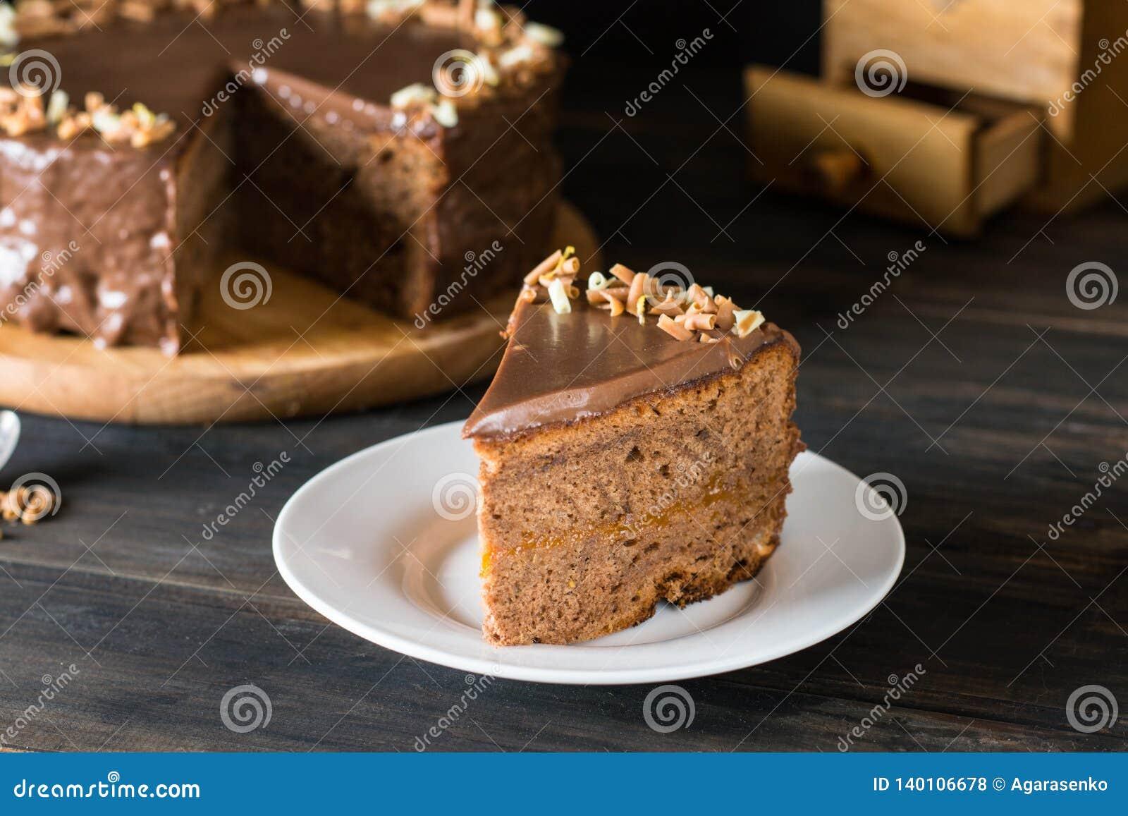 Parte de bolo de chocolate em uma placa branca em de madeira Bolo austríaco tradicional Bolo de Sacher Torta do abricó Conceito d