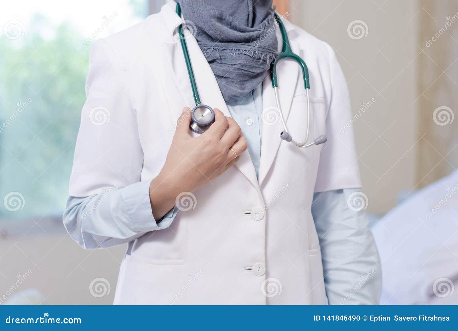 Parte del cuerpo de la vista delantera de la cabeza femenina del estetoscopio de la tenencia de la mano del doctor del hijab dent