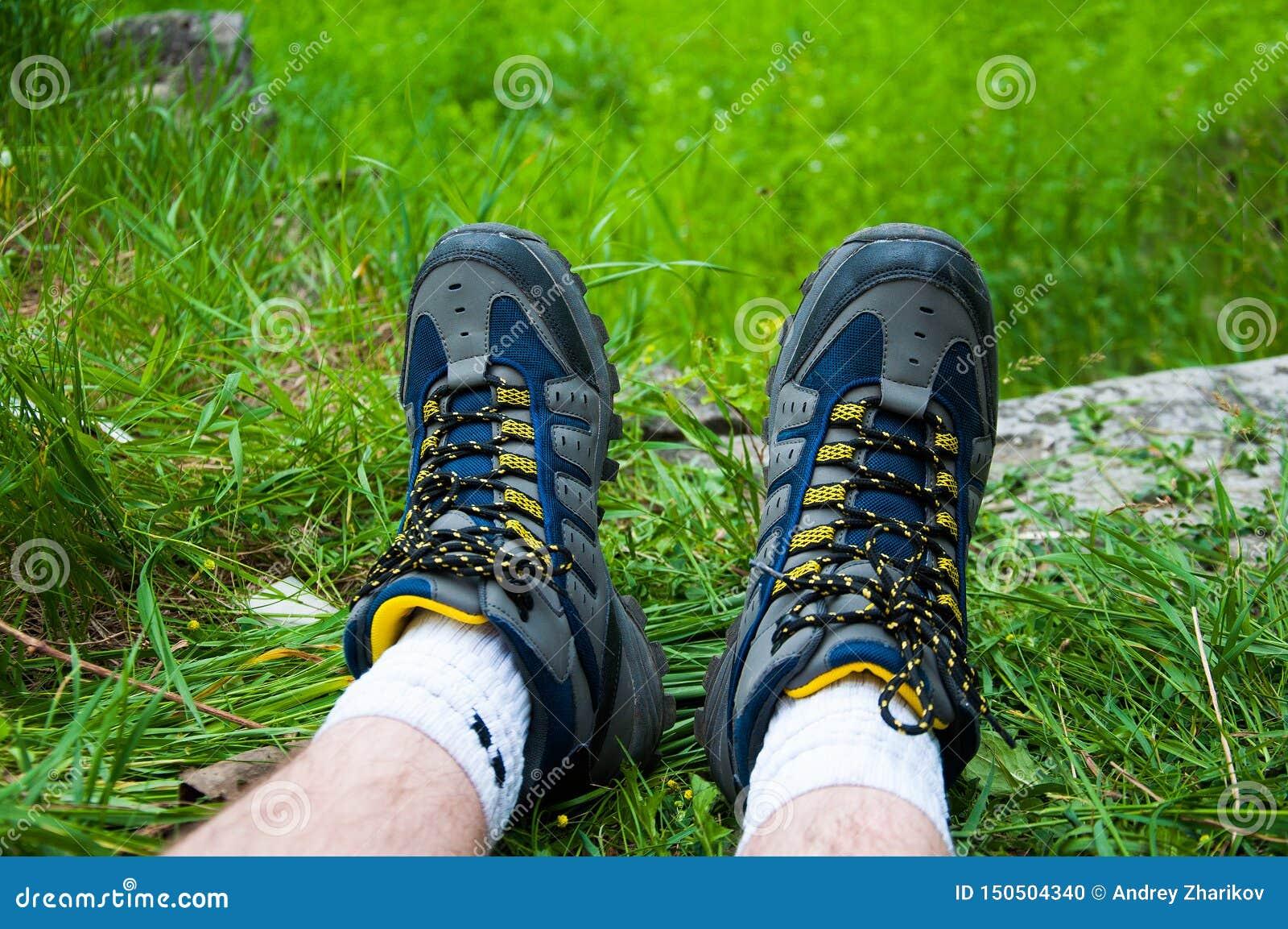 Parte delle gambe dell uomo Negli stivali blu di trekking Sull erba verde