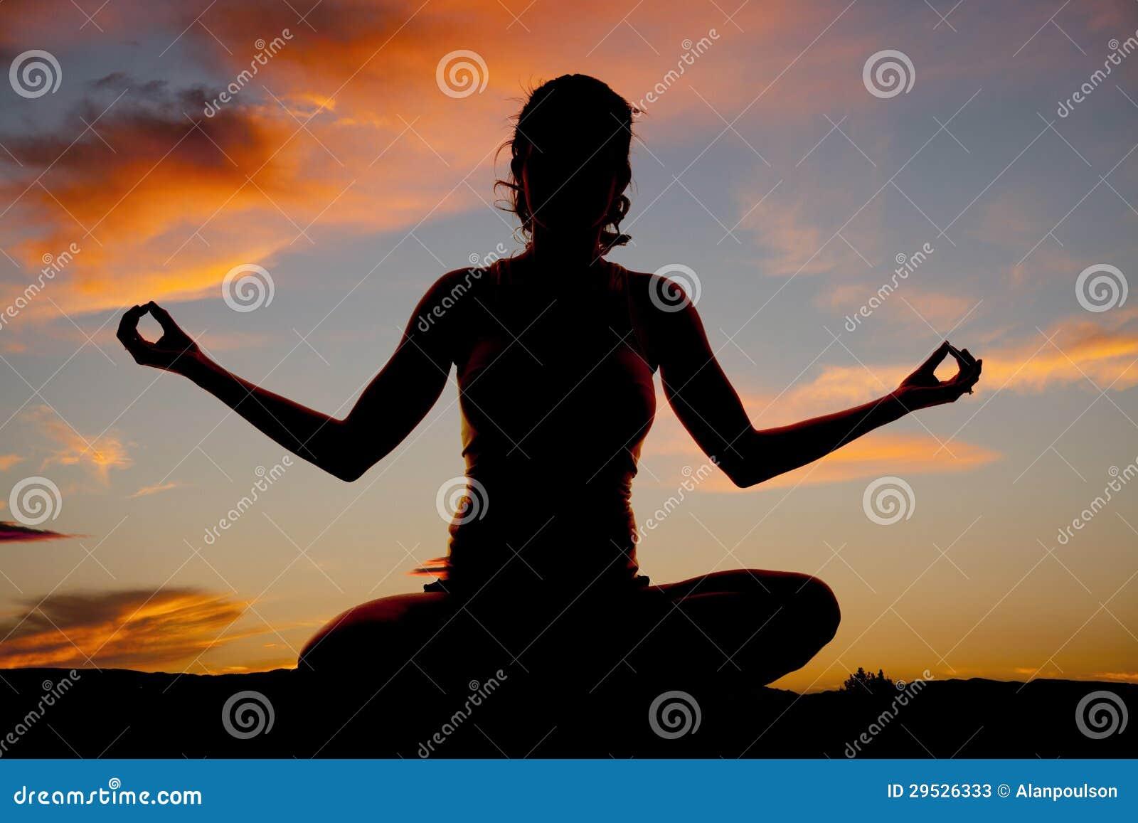A parte dianteira da ioga da mulher da silhueta senta-se