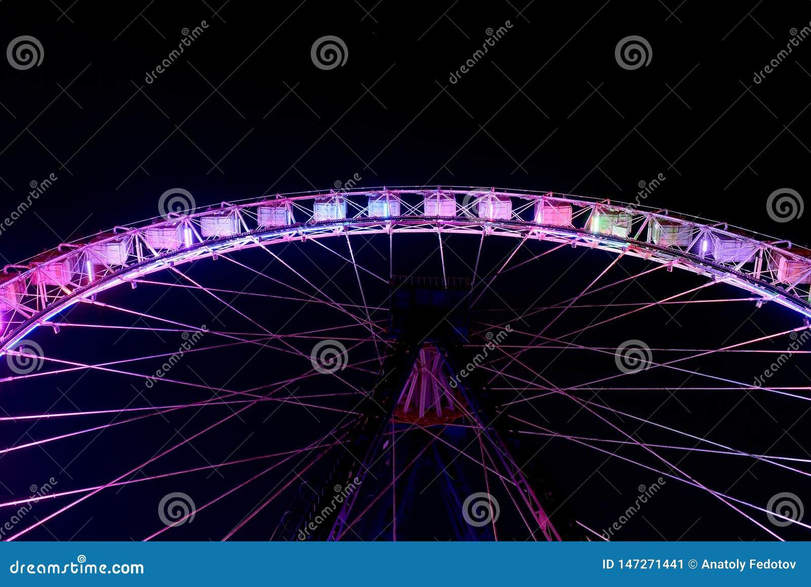 A parte dos ferris roda dentro o funfair na noite