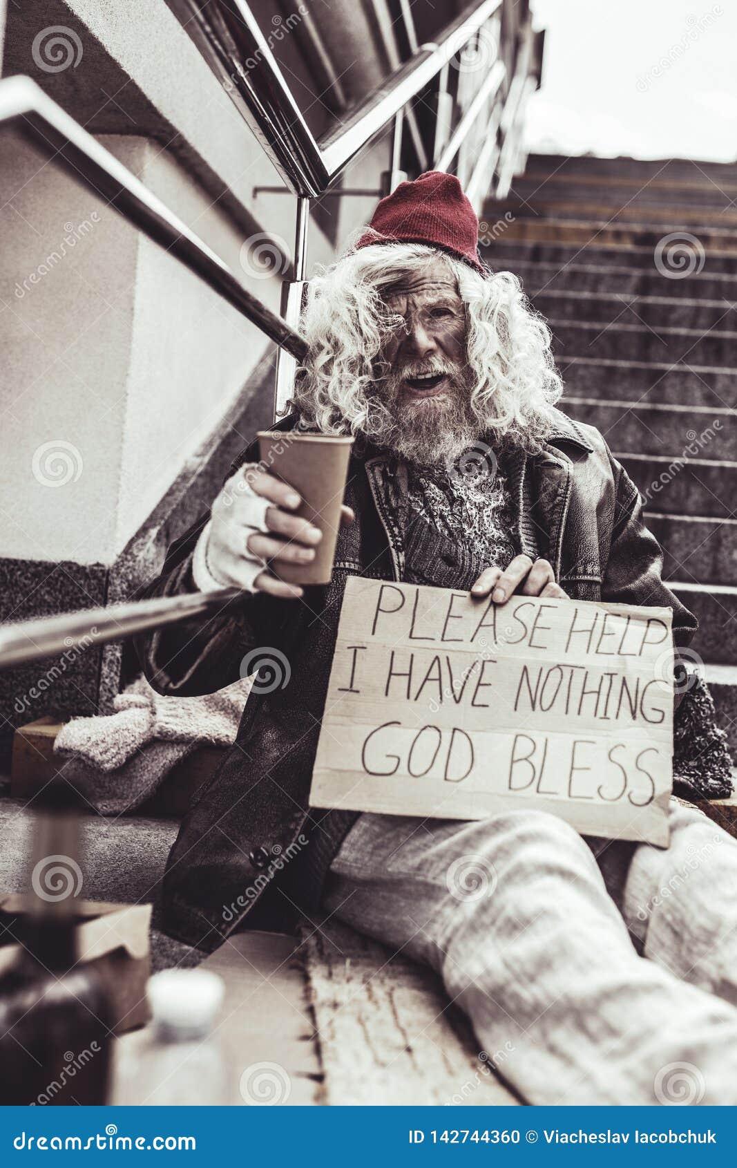 Parte externa do mendigo desesperado e cartaz de assento da escrita que pede a ajuda