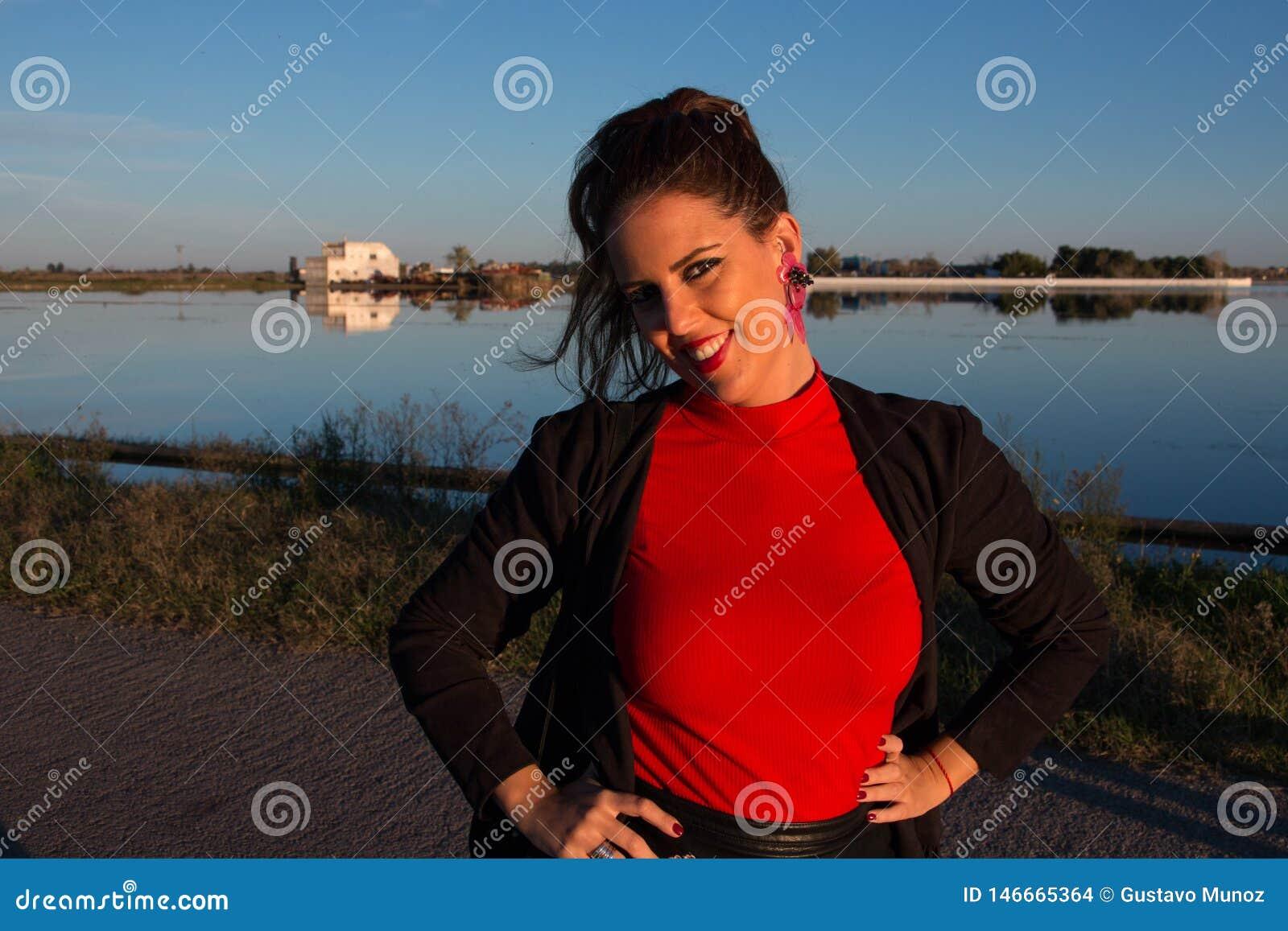 Parte externa moreno bonita da posi??o do retrato da mulher em um dia ensolarado, com um lago no fundo