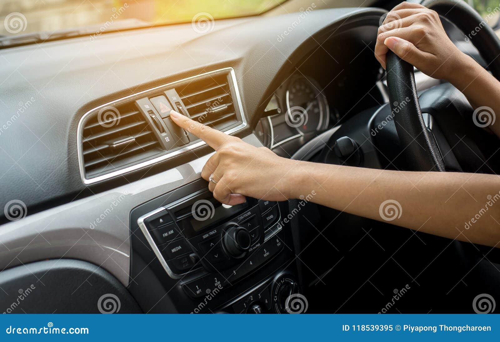 Parte inferior da luz de emergência do carro da imprensa do motorista da mulher da mão ou do dedo no painel