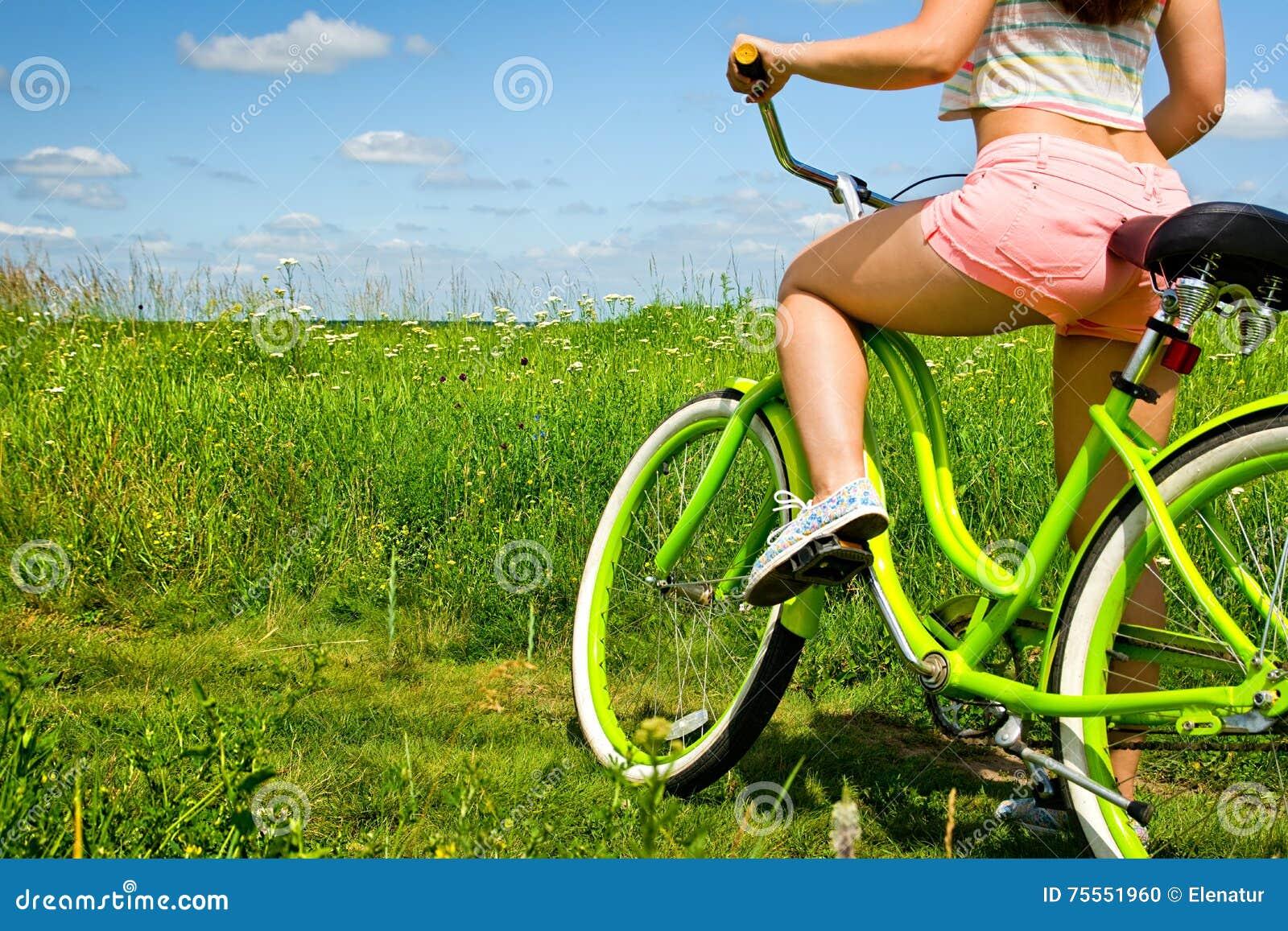 Parte posterior atractiva de la mujer atractiva joven en el crucero de la bicicleta en naturaleza