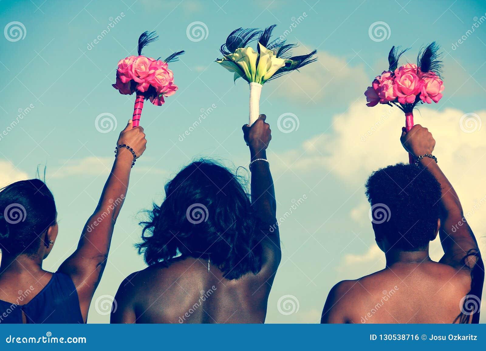 Parte posterior de las mujeres afroamericanas que sostienen ramos coloridos en el aire el día de boda