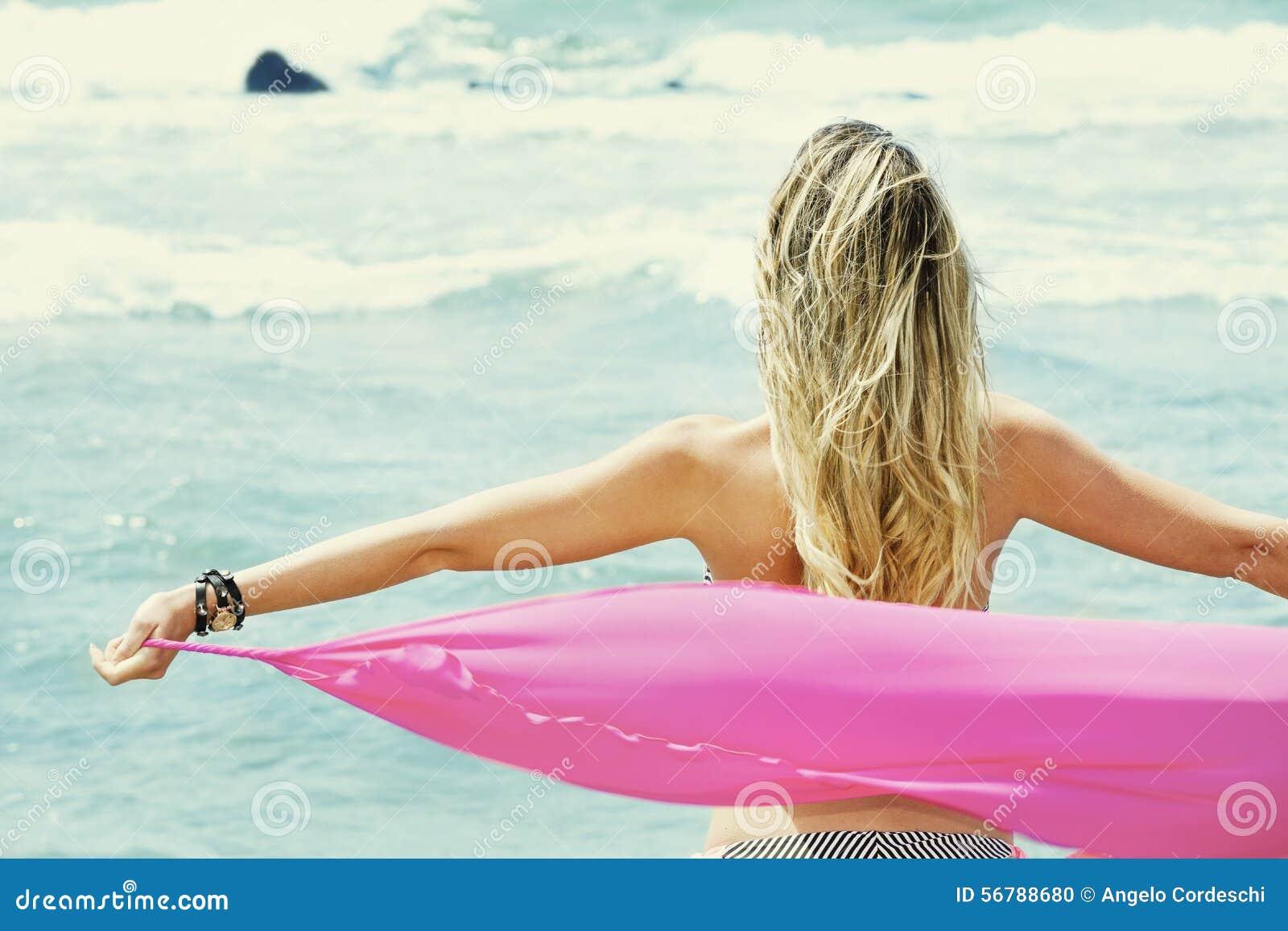 Parte posterior rubia de la mujer joven con los brazos abiertos, tomando un paño de seda que mira el mar