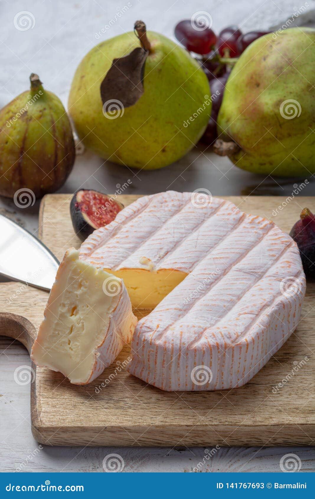 Parte redonda de queijo francês Fleur Rouge feita do leite de vaca servido como a sobremesa com figos e as peras frescos
