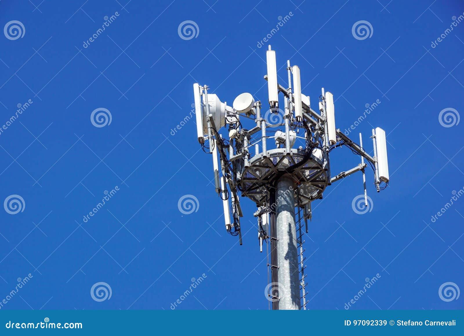 Parte superior de la torre de comunicación del teléfono celular con las antenas múltiples contra un cielo azul