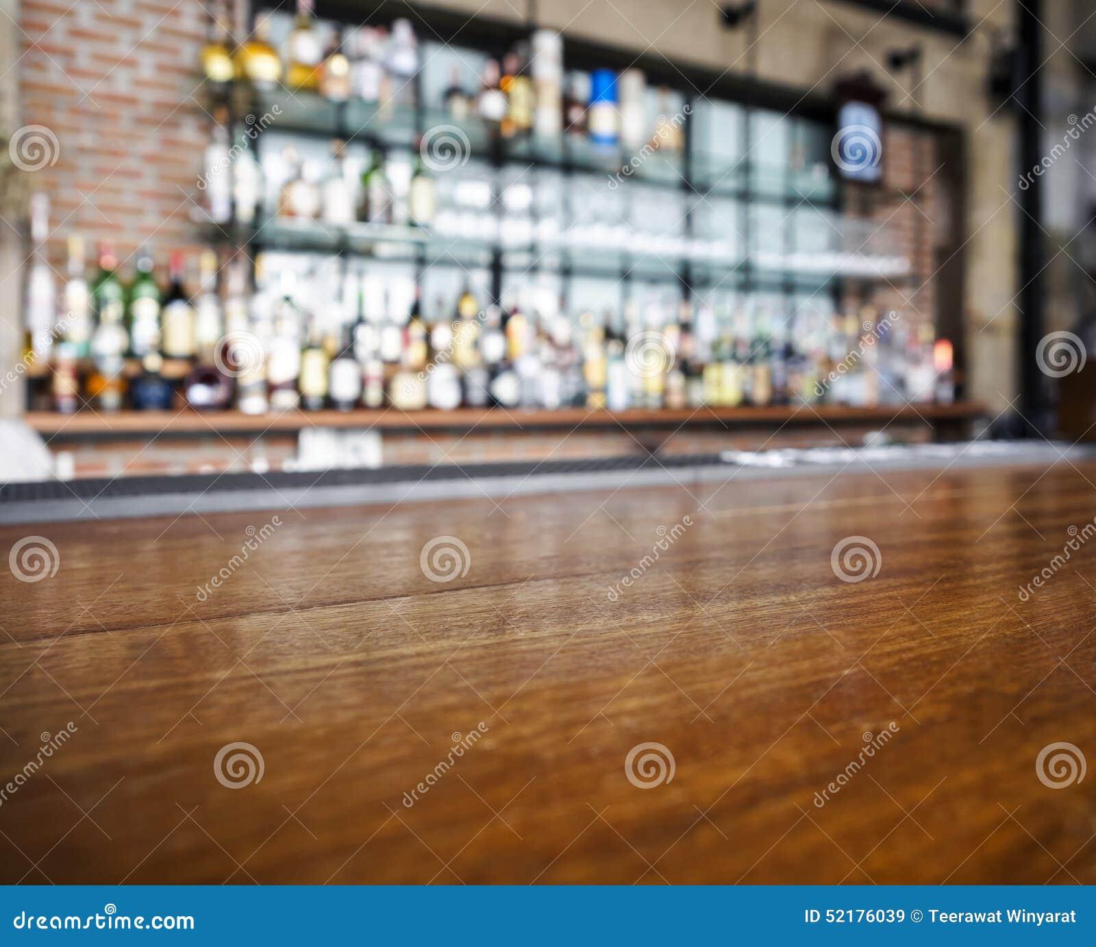 Parte superior do contador de madeira da tabela com fundo borrado da barra