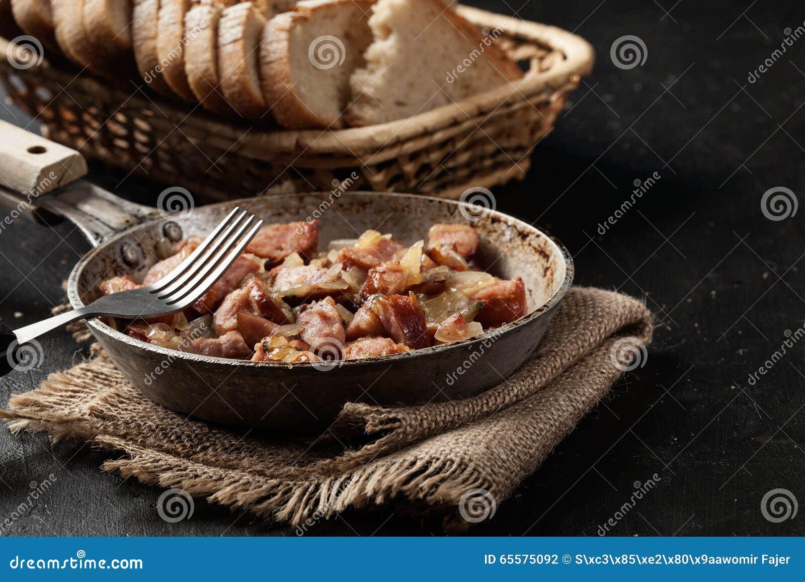 Partes de salsicha fritadas com cebolas