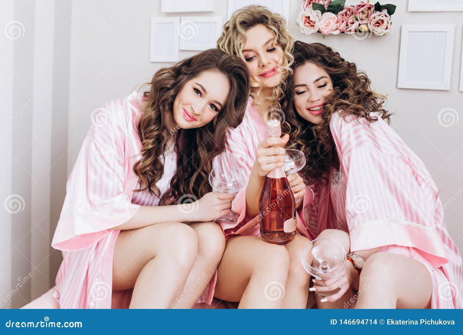 Parti f?r flickor Flickv?nner dricker rosa champagne f?r den gifta sig ceremonin i rosa pyjamas