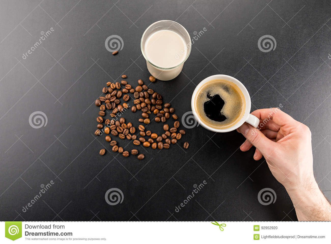 Partial top view of person holding cup of fresh espresso coffee