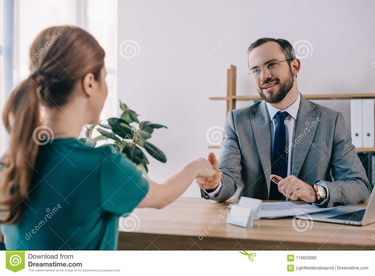 partial view of businessman and client shaking hands during meeting