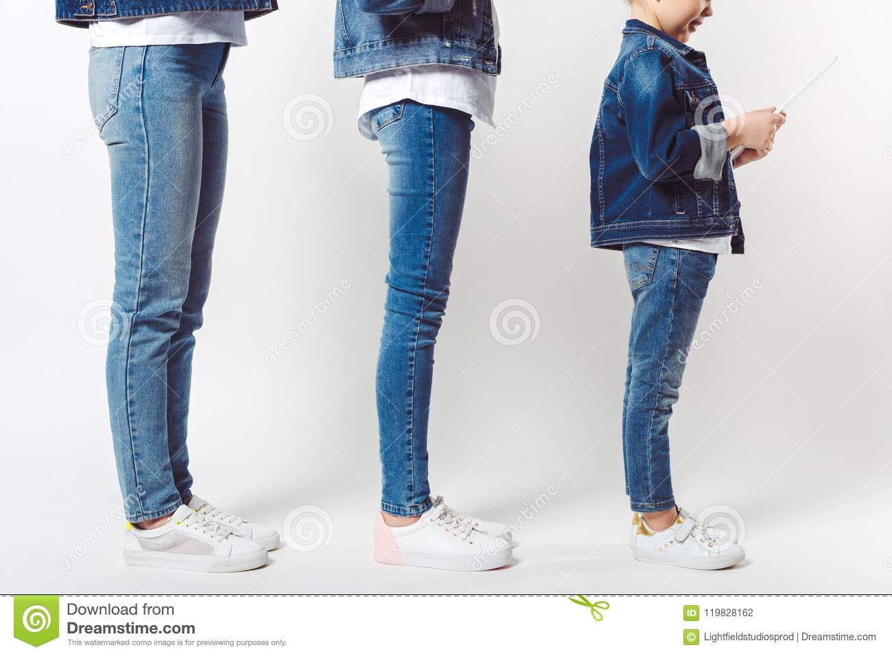 partial view of family and kid with tablet in similar denim clothing standing in row