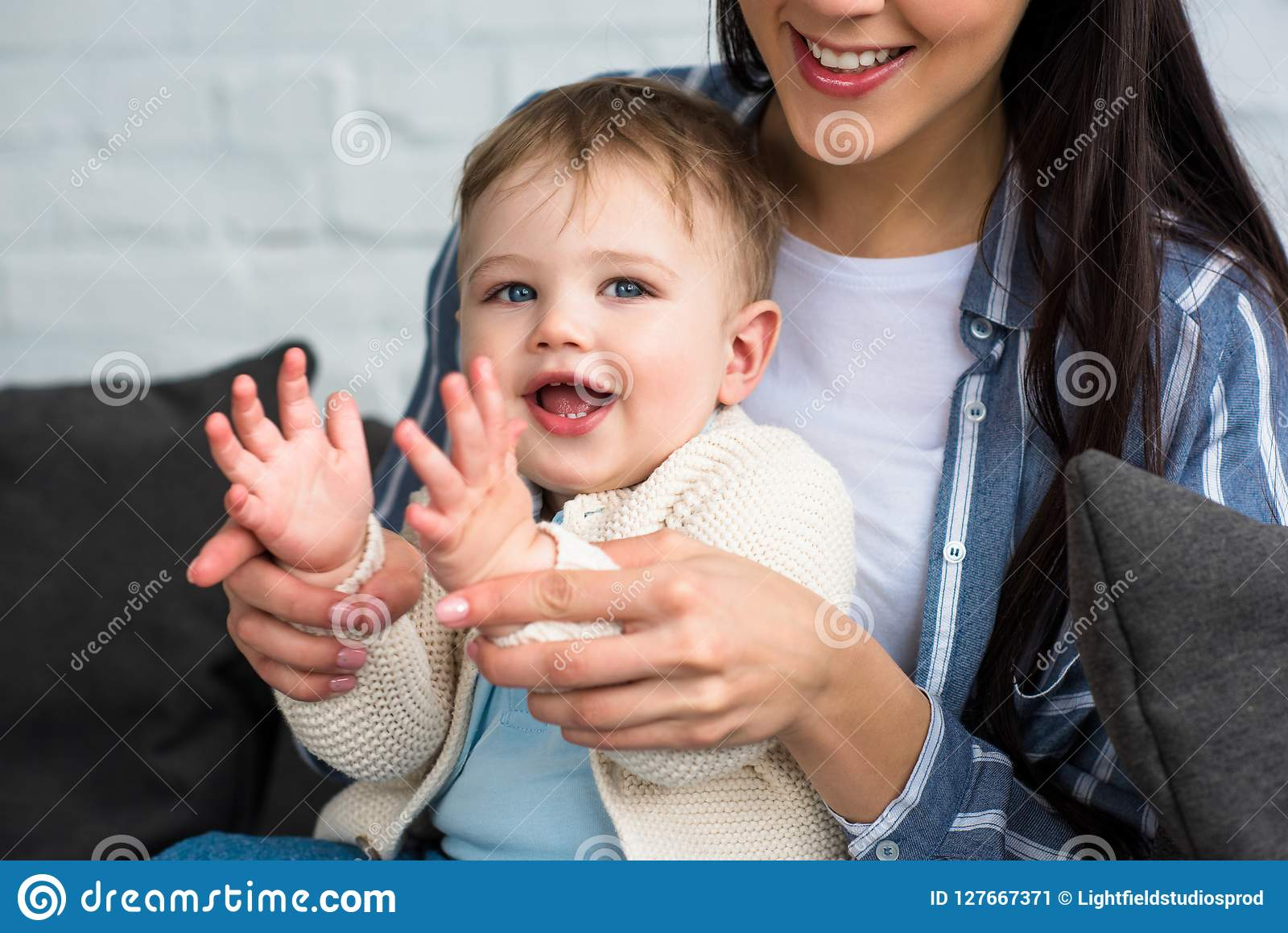 partial view of smiling mother playing with little baby