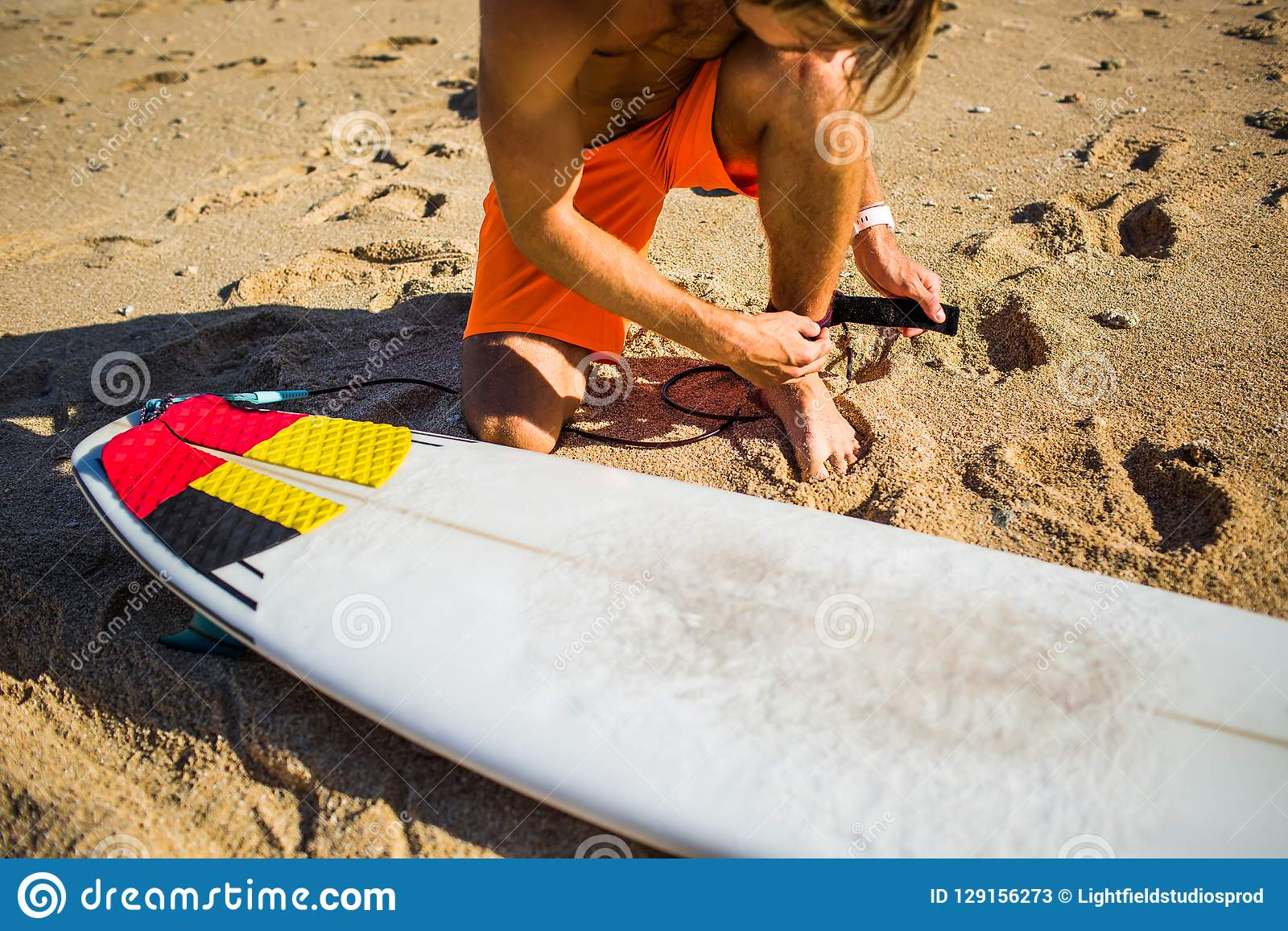 partial view of sportsman getting ready for surfing
