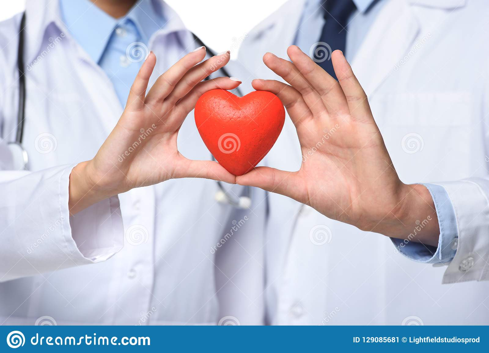 partial view of two doctors holding red heart in hands
