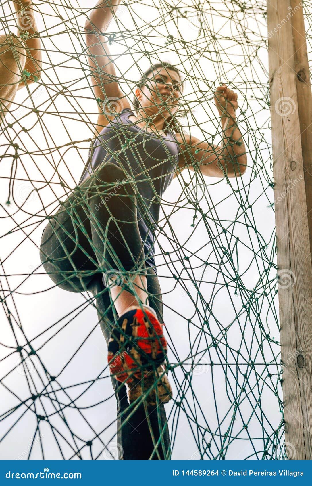 Participante na rede de escalada do curso de obstáculo