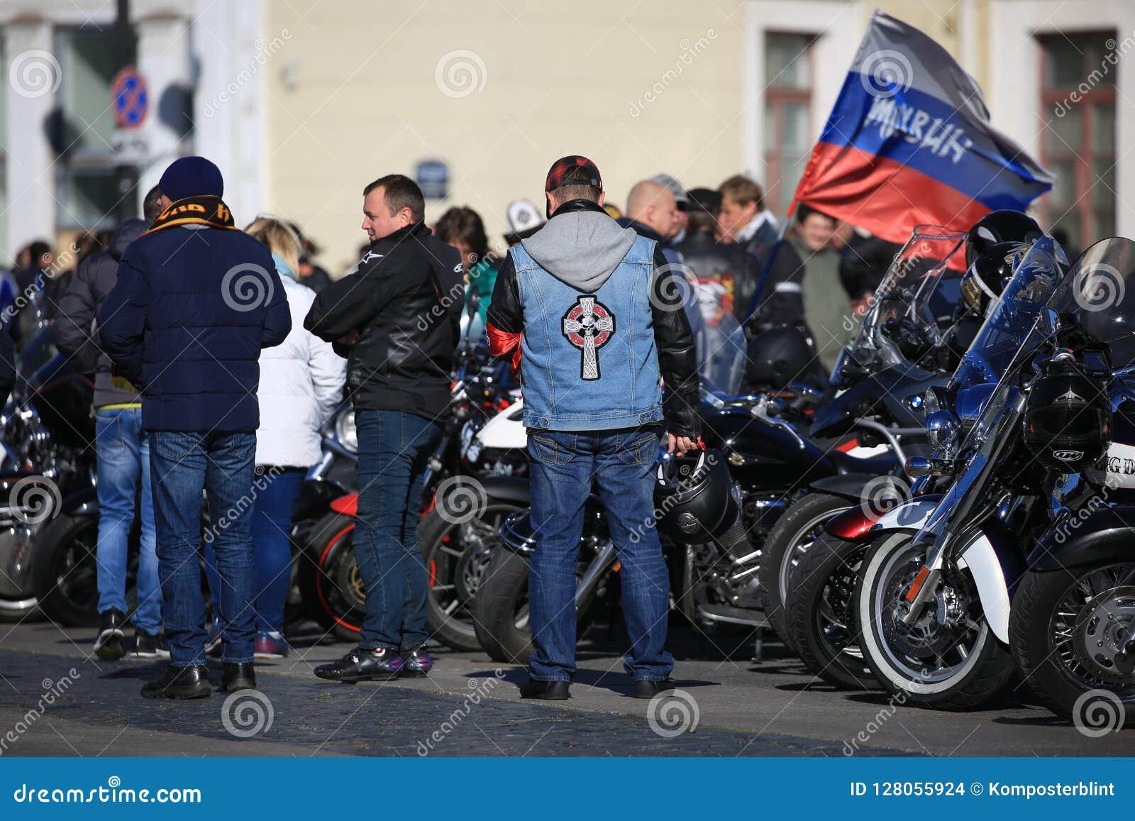 Participantes del movimiento del motorista de la ciudad de Tikhvin con sus motocicletas cerca de la pared del edificio del estado