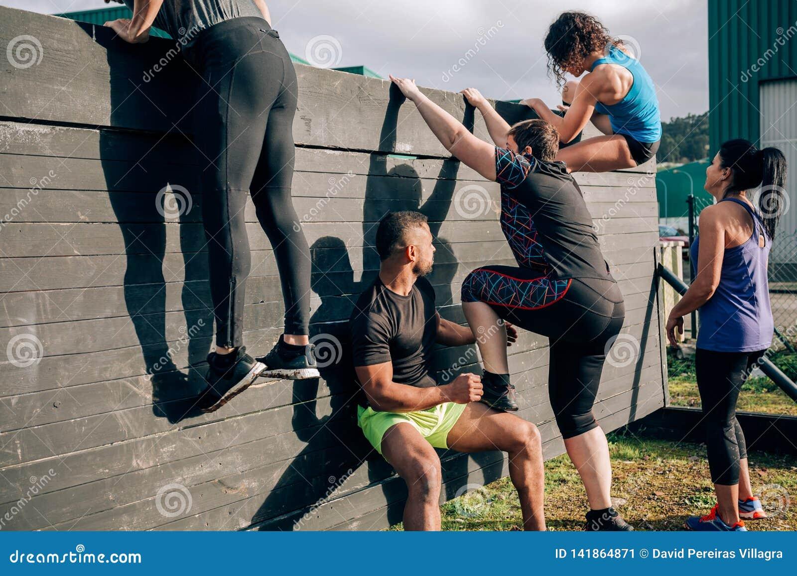 Participantes na parede de escalada do curso de obstáculo