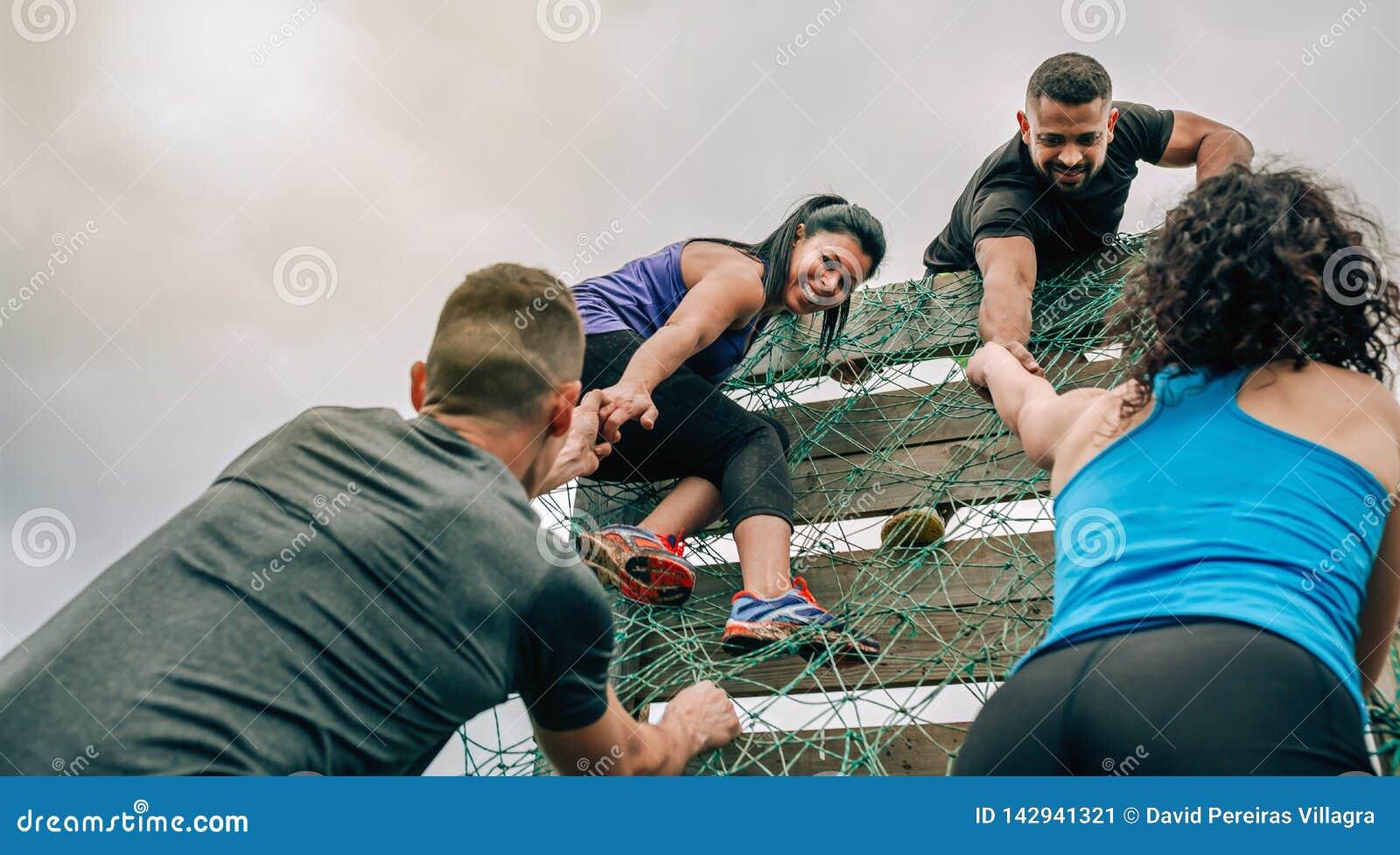 Participantes na rede de escalada do curso de obstáculo