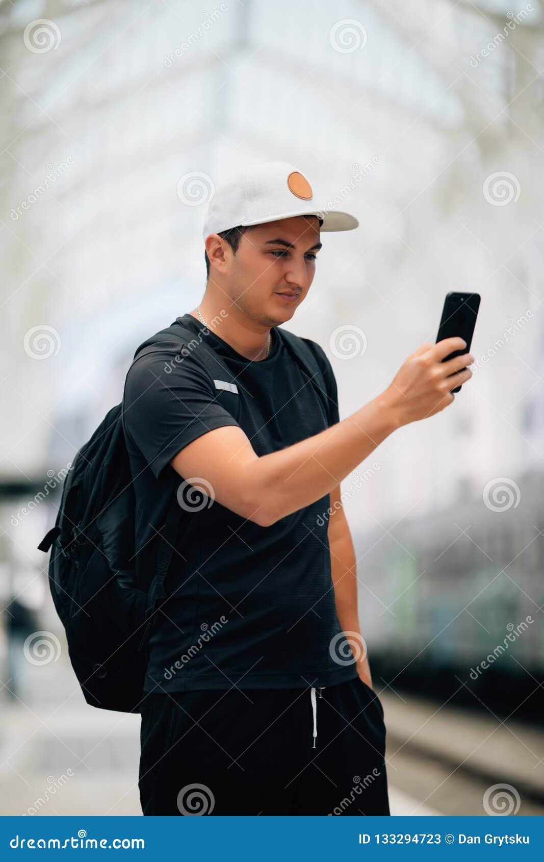 Participation de jeune homme utilisant le téléphone avec la position de sac à dos sur la plate-forme à la station de train Concep