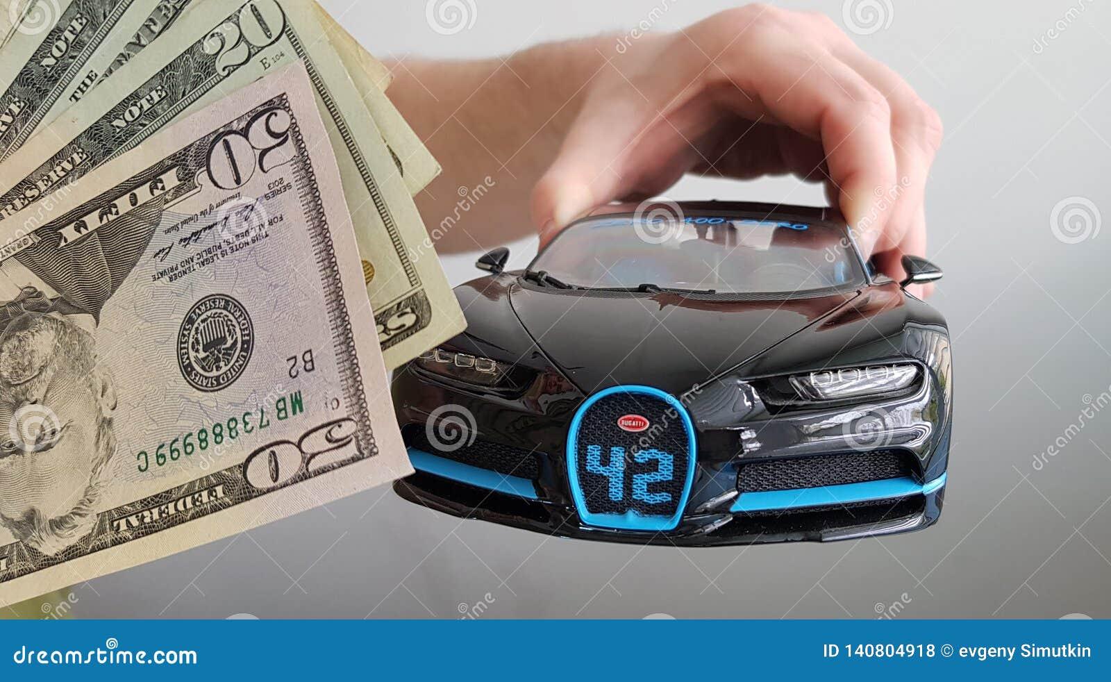 Participation masculine de main dans le jouet noir en métal de voiture de Bugatti Chiron d air sur le fond blanc