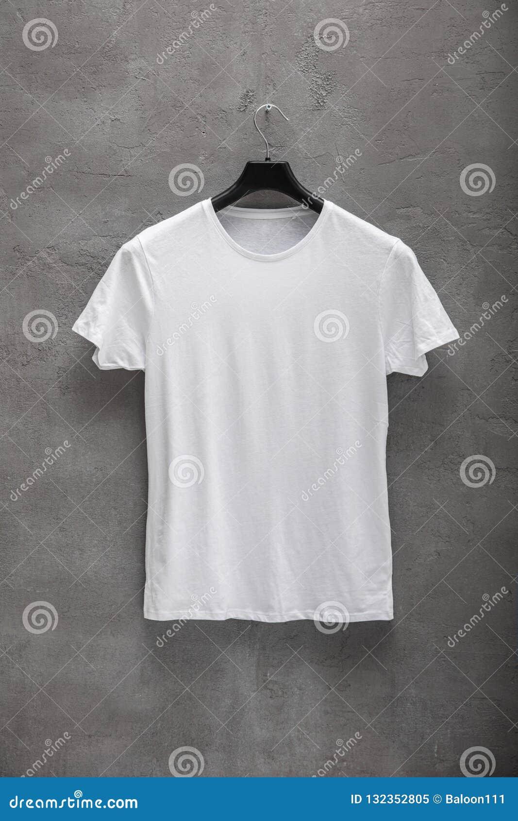 Partie antérieure du T-shirt blanc masculin de coton sur un cintre et un mur en béton à l arrière-plan