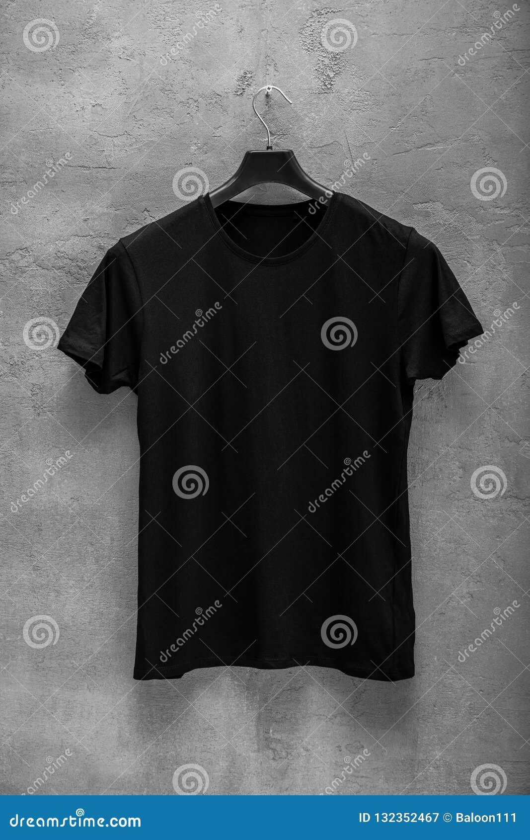 Partie antérieure du T-shirt noir masculin de coton sur un cintre