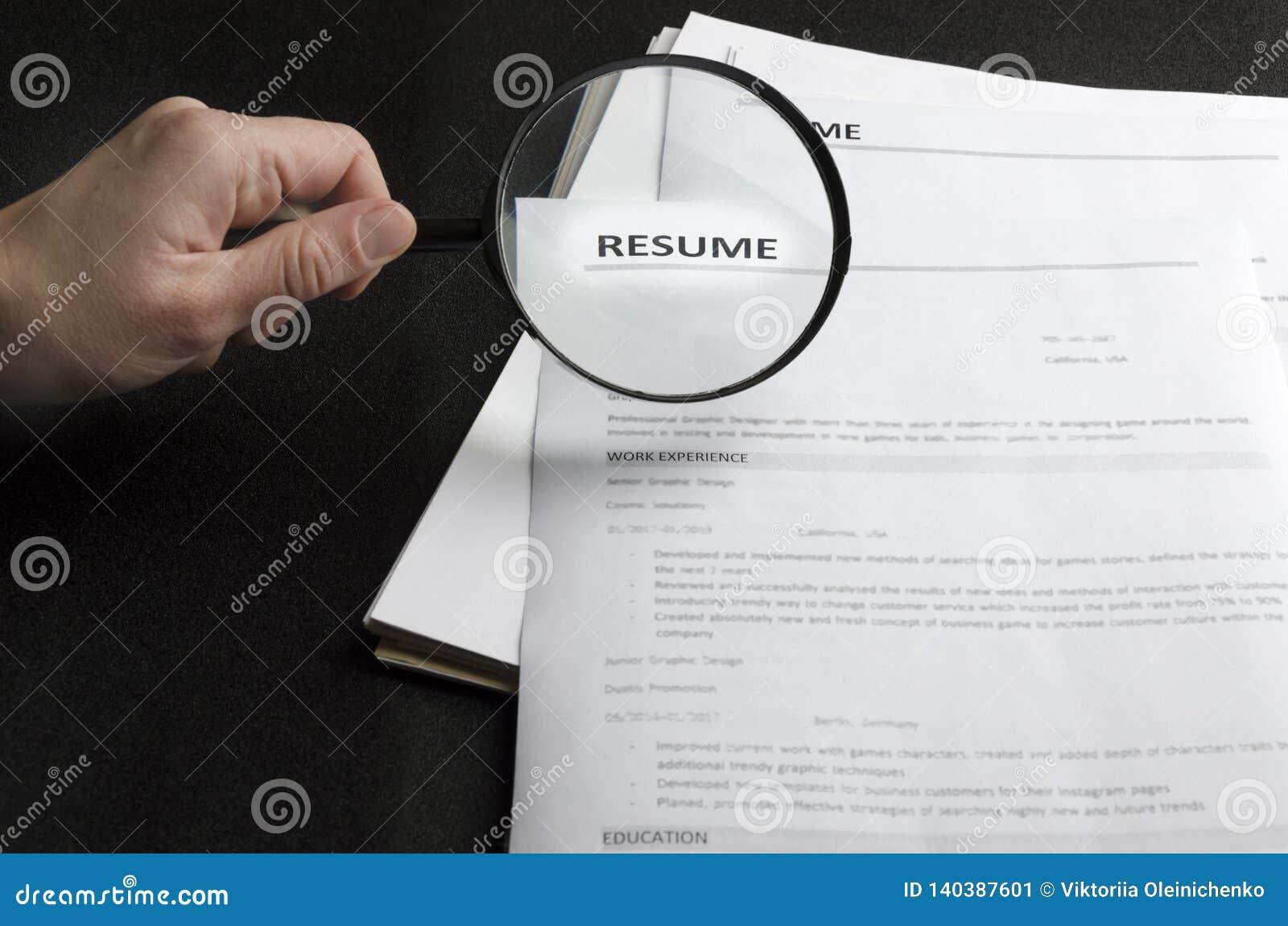 Partij van samenvattingstoepassingen op het zwarte bureau, u-holdingsvergrootglas, concept het zoeken van professionele werknemer