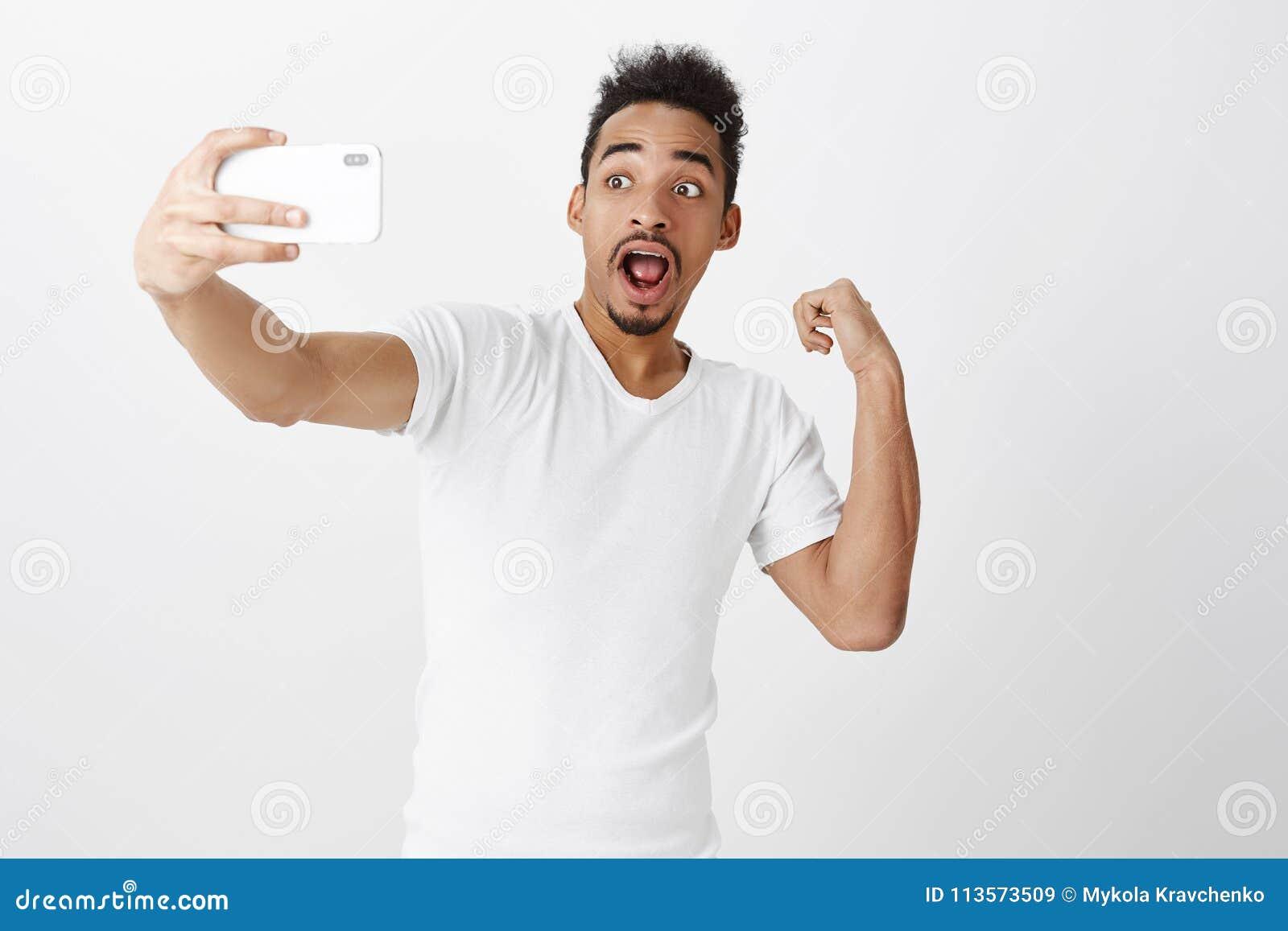 Partilha com os seguidores que oprimem notícias Blogger de pele escura chocado entusiasmado, puxando a mão com o smartphone, apon