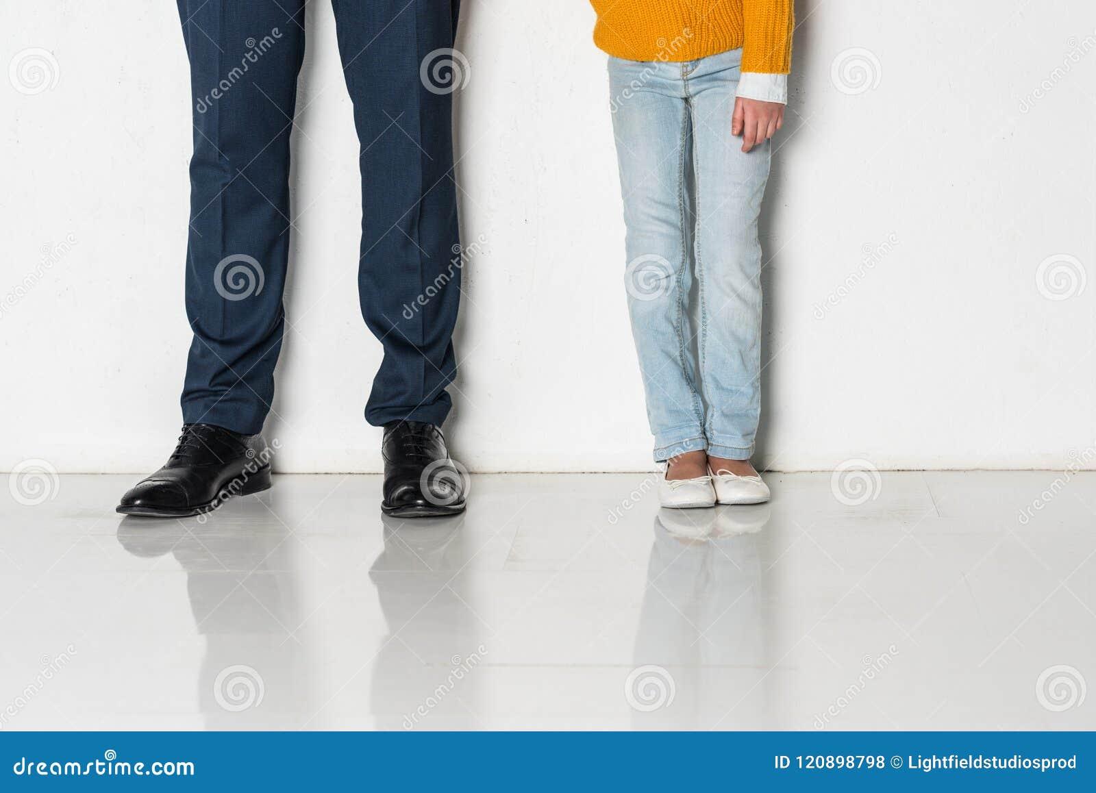 Partisk sikt av dottern och fadern i händer för innehav för affärsdräkt