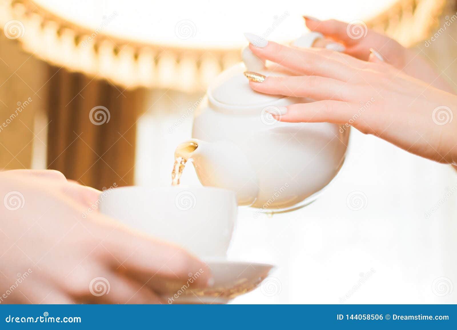 Partito di tè Le donne versano il tè verde in una tazza bianca