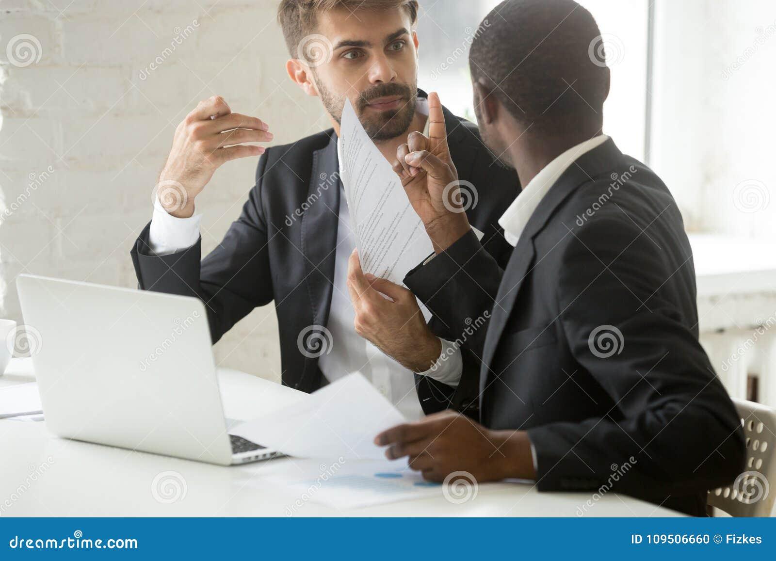 Partner africani e caucasici multirazziali che discutono a stante in disaccordo