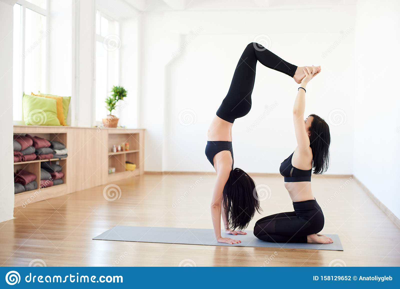 Partner Yoga. Side View Of Flexible Women Helping Each Other