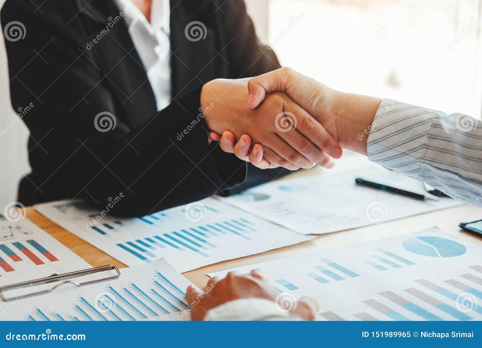 Partnercollega s die handen schudden die nieuwe de Financiën en de Economiegrafiek van het startprojectplan met succesvol laptop