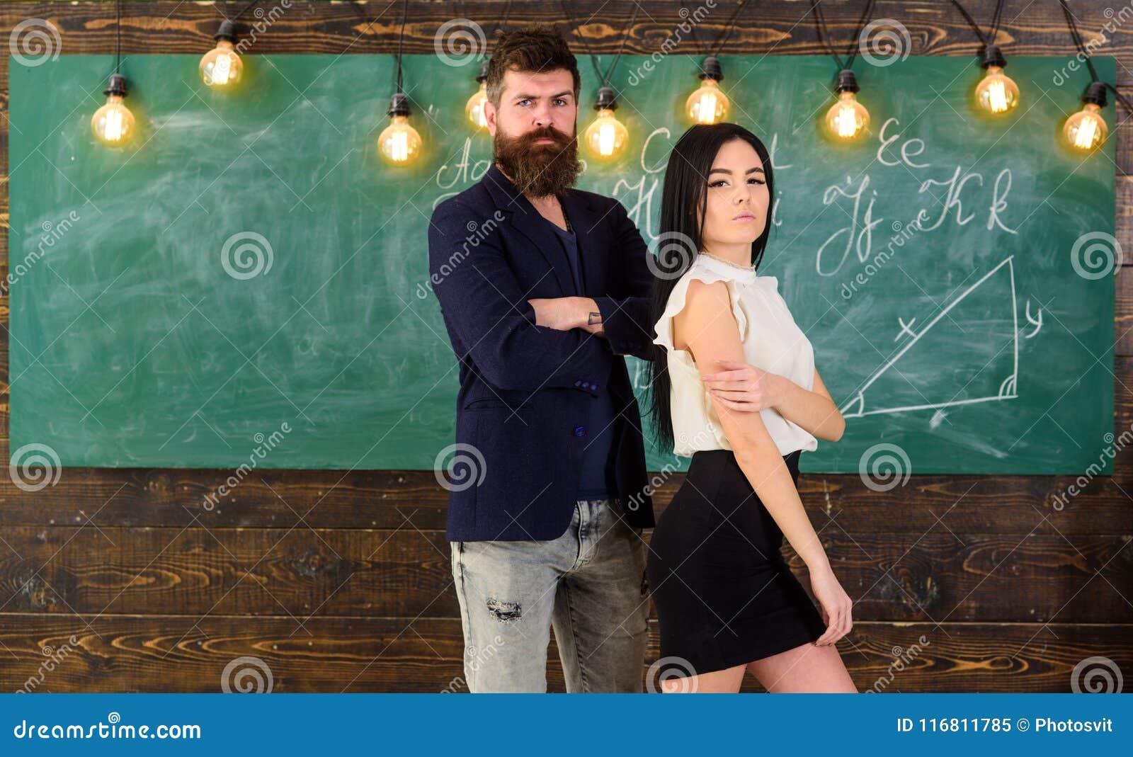 Partners il concetto L uomo con la barba e l insegnante sexy della ragazza stanno in aula, lavagna su fondo Signora e pantaloni a