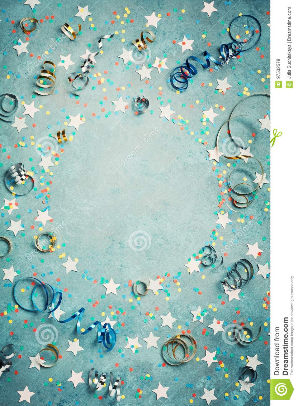 Party, carnival or birthday frame with colorful confetti and streamer on vintage blue table top view. Flat lay style. Holiday.