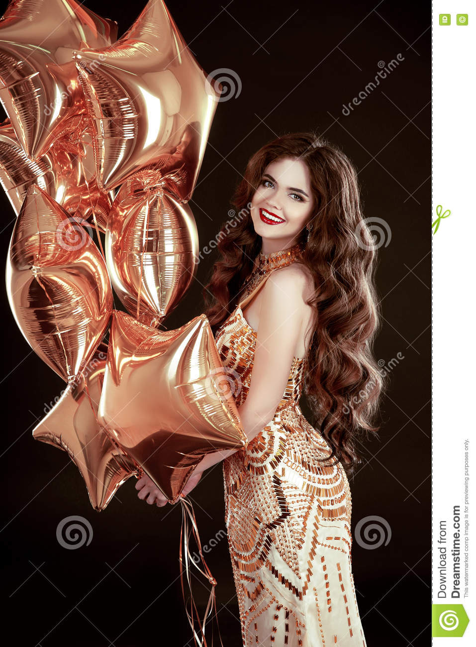 Party. Happy brunette girl with golden star balloons wears in elegant dress isolated on black studio background.