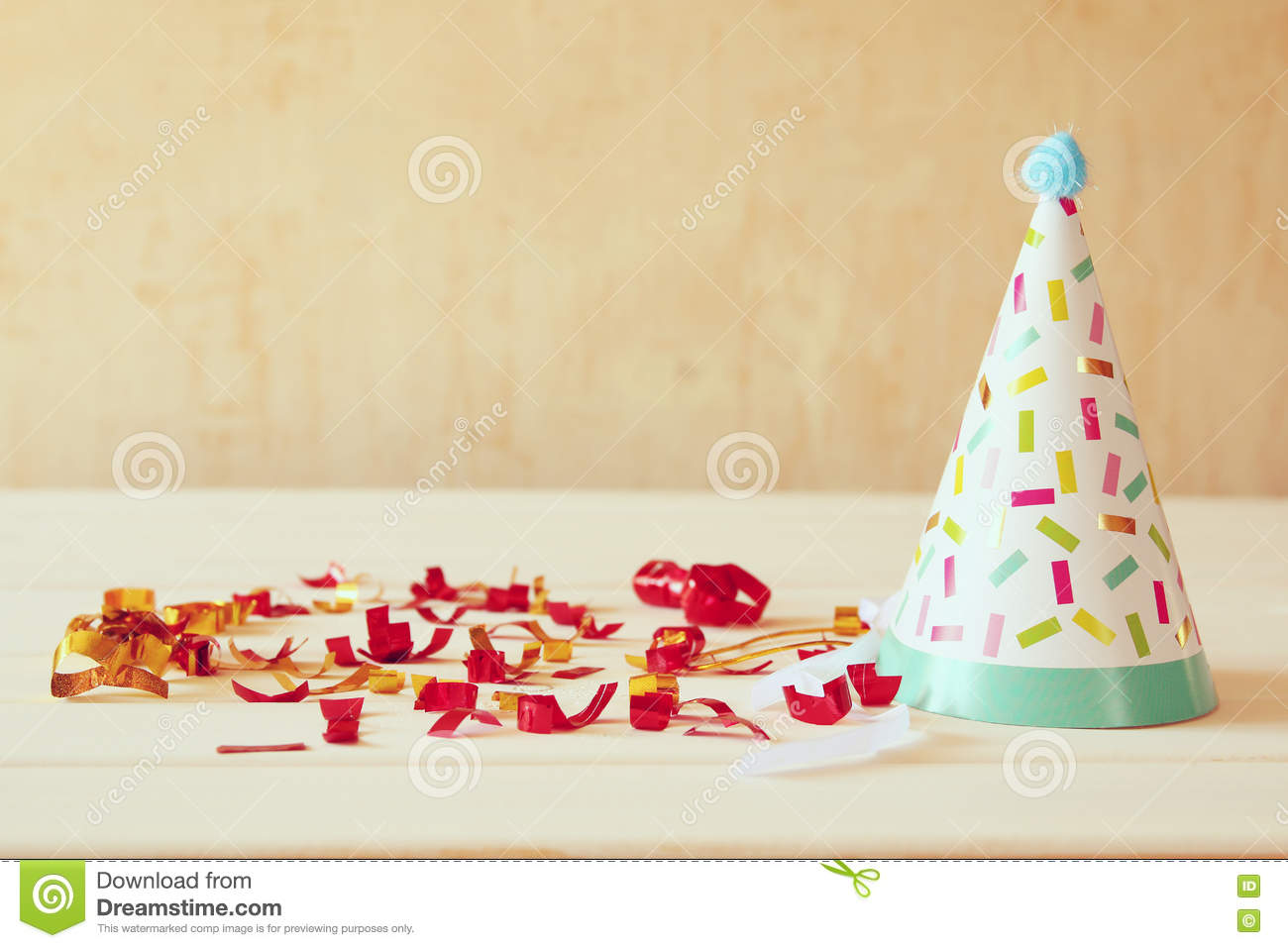 Party hat next to colorful confetti on wooden table.