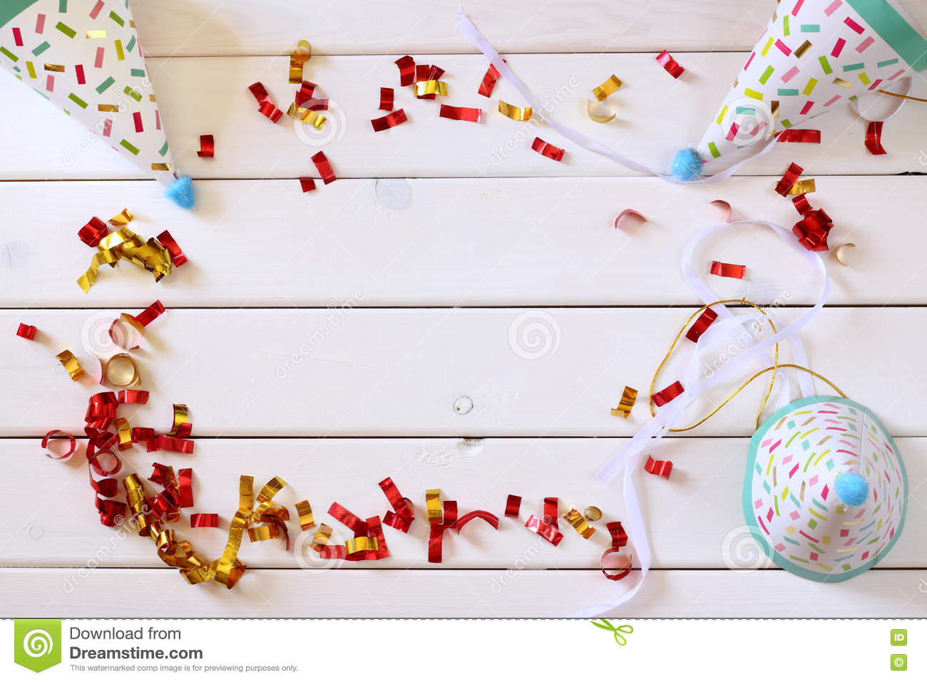 Party hat next to colorful confetti on wooden table