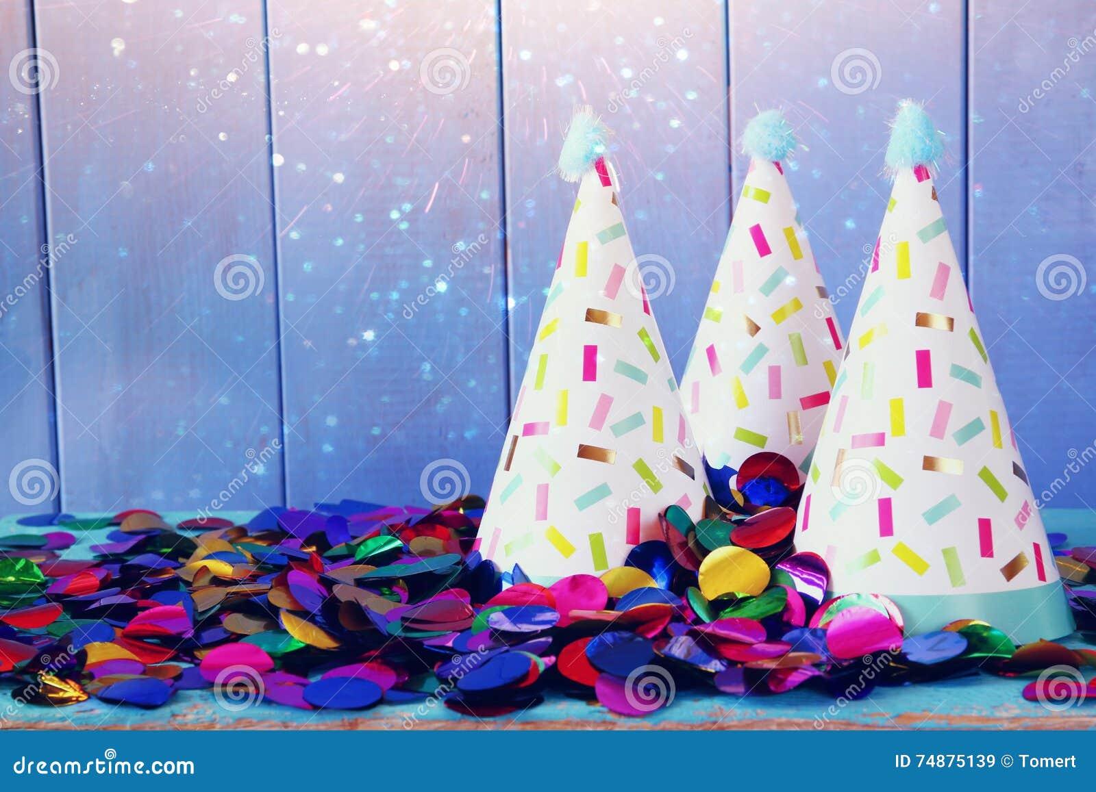 Party o chapéu e confetes coloridos na tabela de madeira